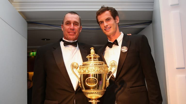 Andy Murray posing in front of a trophy