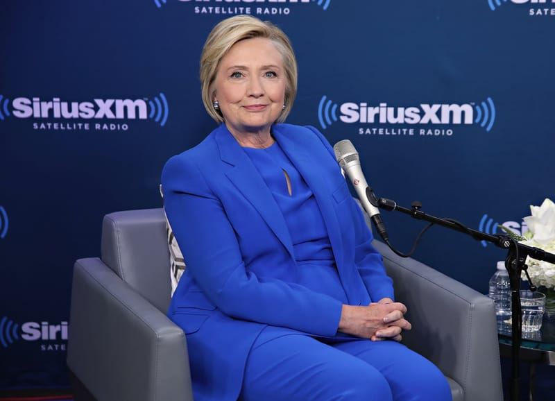 Hillary Clinton sat in front of a microphone