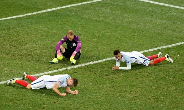 Three football players laying on the pitch looking disappointed