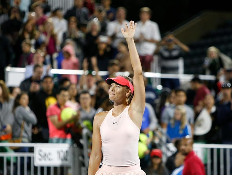 Maria Sharapova standing on court with her arm in the air